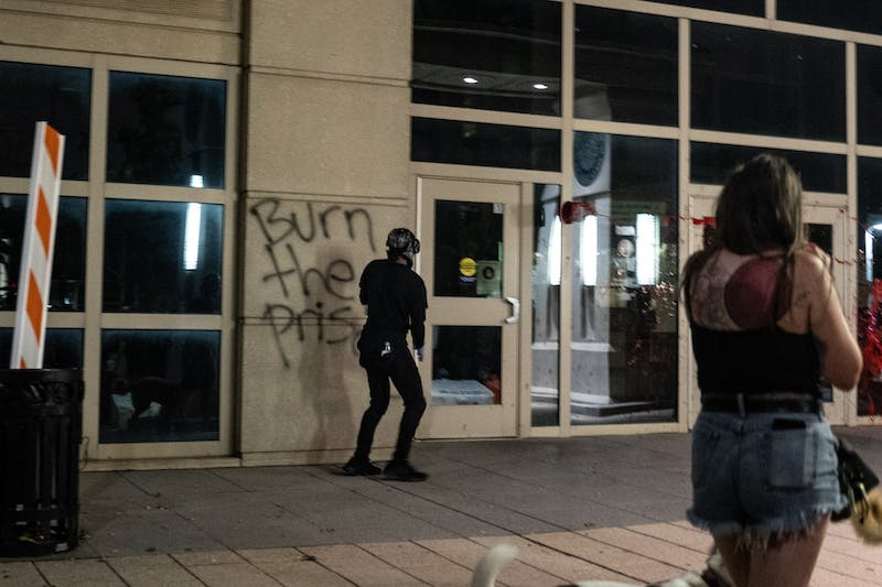 """A protestor stands in front of the recently-spray painted words, """"Burn the Prisons,"""" as a bucket of red paint flies toward the building during the Raleigh Black Lives Matter protest on Friday, Aug. 28, 2020."""