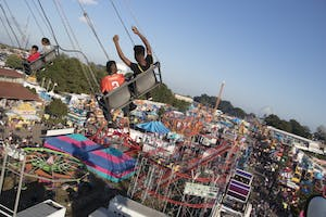 Two children ride the swing ride, overlooking the entire midway.
