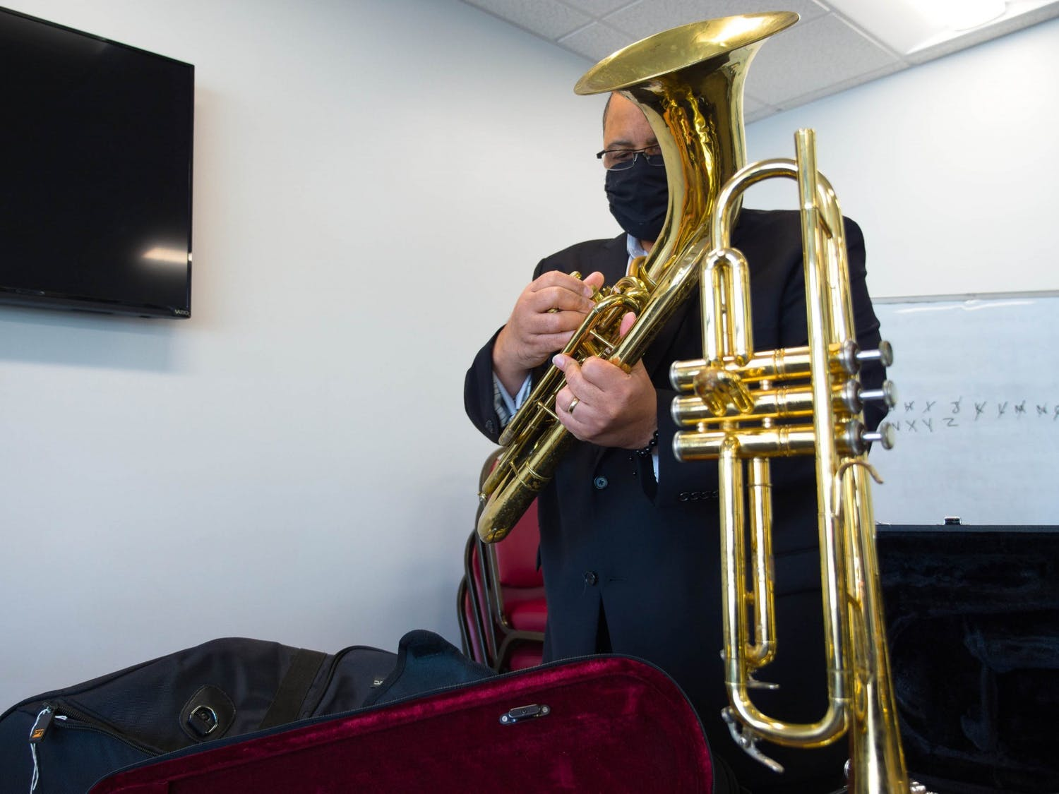 Ralph Barrett, an Assistant Professor of NC Central University's Music Department, checks the condition of the valves on a donated instrument in the YouthWorx conference room on Wednesday, Dec. 9, 2020. Barrett is a member of Musical Empowerment's Board of Directors.