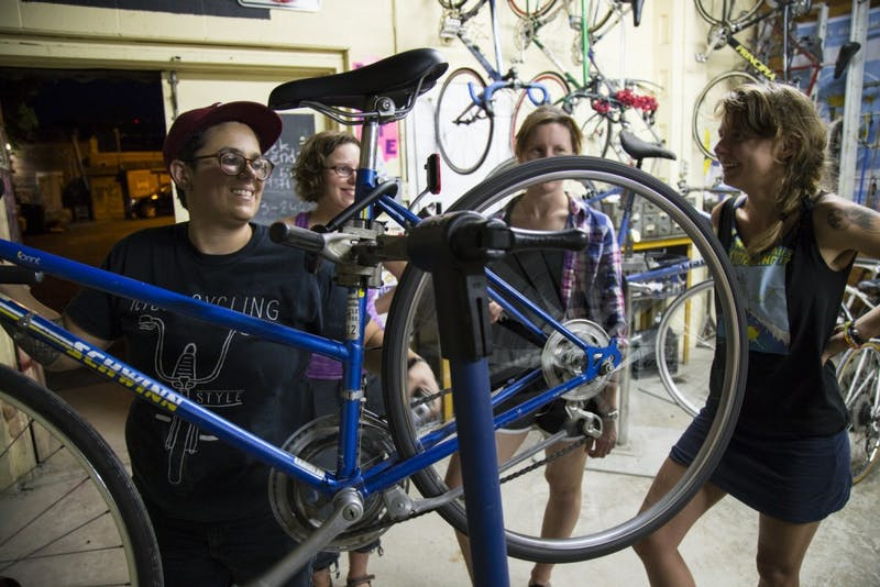 """(Left to right) Ryann Giorgi, Maia Call, Victoria Petermann, and Jolie Day work on maintenance for Call's bike. Day, one of Moon Cycle's founders, said """"I wanted to learn how to work on bikes with my friends, and in an environment where I didn't feel like I was being judged because I didn't know how to do everything on a bike."""""""