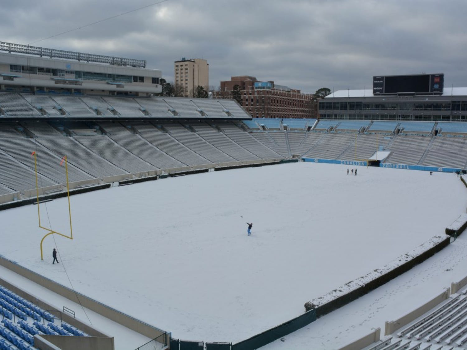 Students play football in a snow covered Kenan Stadium.