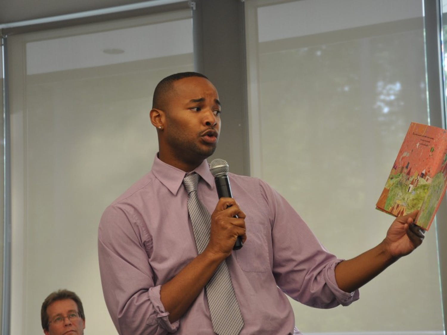 """Omar Currie, a former teacher at Efland Cheeks Elementary school, reads from children's book""""King and King"""" at the Chapel Hill Public Library. Currie resigned from the school after a controversy emerged over Currie reading the book, which features amarriage between gay characters, to his third-grade class."""