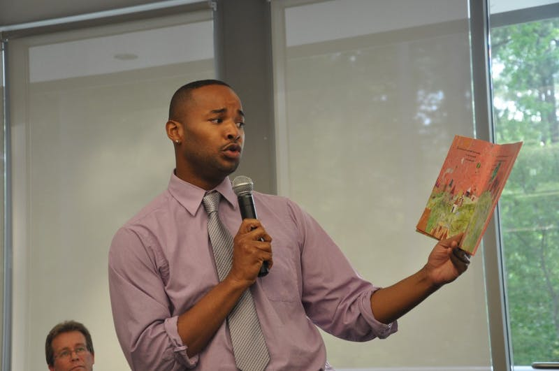 "Omar Currie, a former teacher at Efland Cheeks Elementary school, reads from children's book ""King and King"" at the Chapel Hill Public Library. Currie resigned from the school after a controversy emerged over Currie reading the book, which features a marriage between gay characters, to his third-grade class."