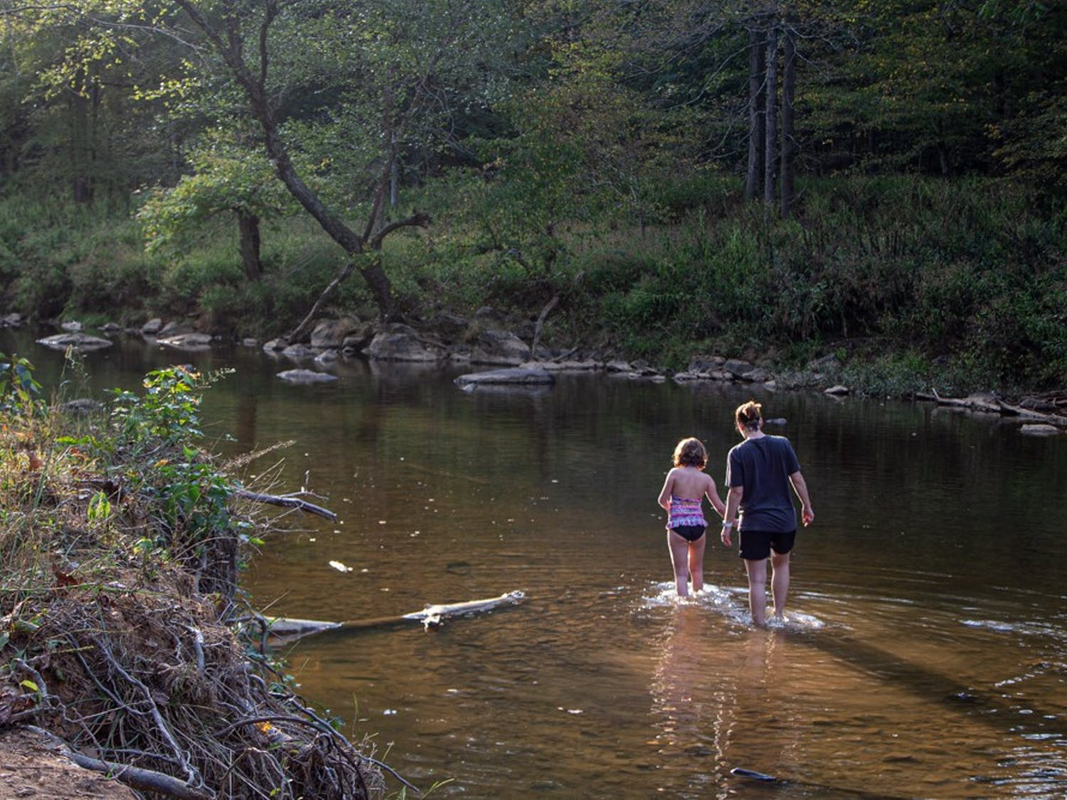 Durham residents Makayla Perry (8) and Beth Revueltas (36) wade in Eno River along Fanny's Ford Trails in Hillsborough on Monday, Sept. 30, 2019.