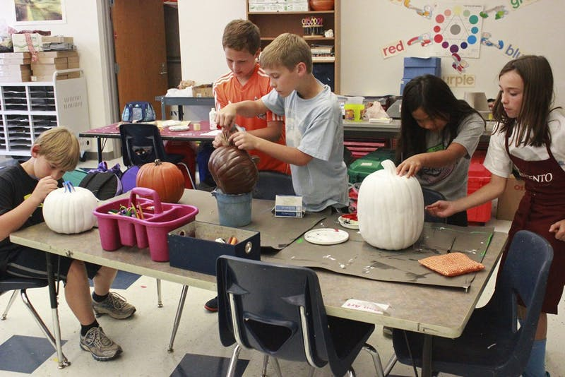 "5th grade Art Club students at Morris Grove Elementary painted pumpkins on Tuesday after school for a pumpkin sale that will raise money for United Way. Art Club teacher, Mrs. Becky Springer, said the inspiration for the fundraiser came because ""I'm just always looking for a creative outlet for the students...and then it just happened to coincide with United Way."""