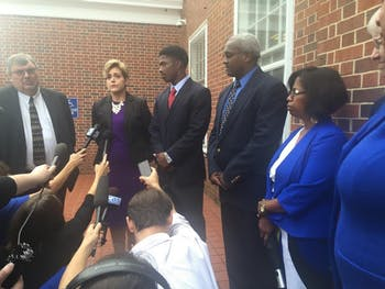 Allen Artis, surrounded by his lawyer and parents, speaks to the media after his court appearance.