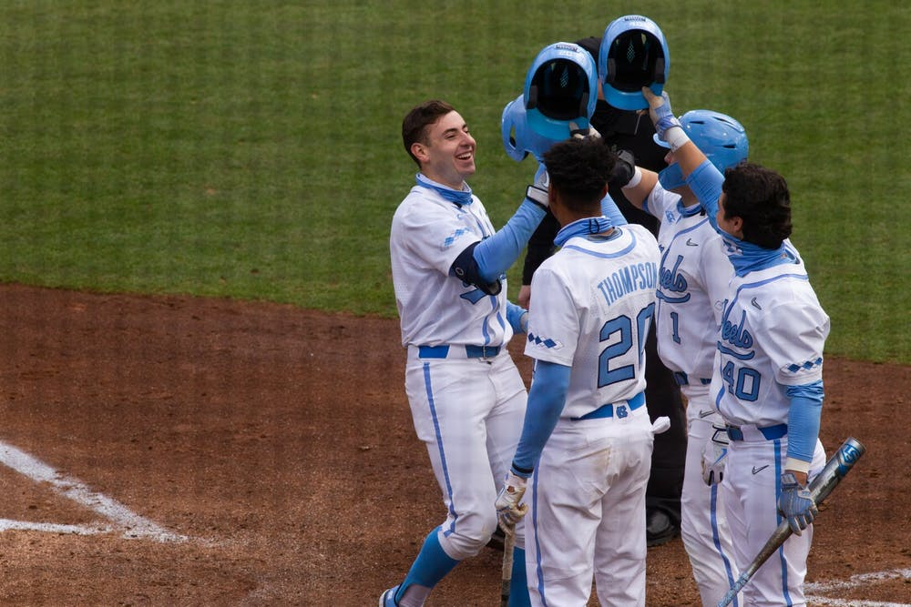 UNC sophomore outfielder Caleb Roberts celebrates his second of two home runs with teammates Justice Thompson (20), Angel Zarate (4) and Danny Seretti (1) during Carolina's 8-1 season-opening victory over James Madison at Boshamer Stadium, Feb. 19, 2021.