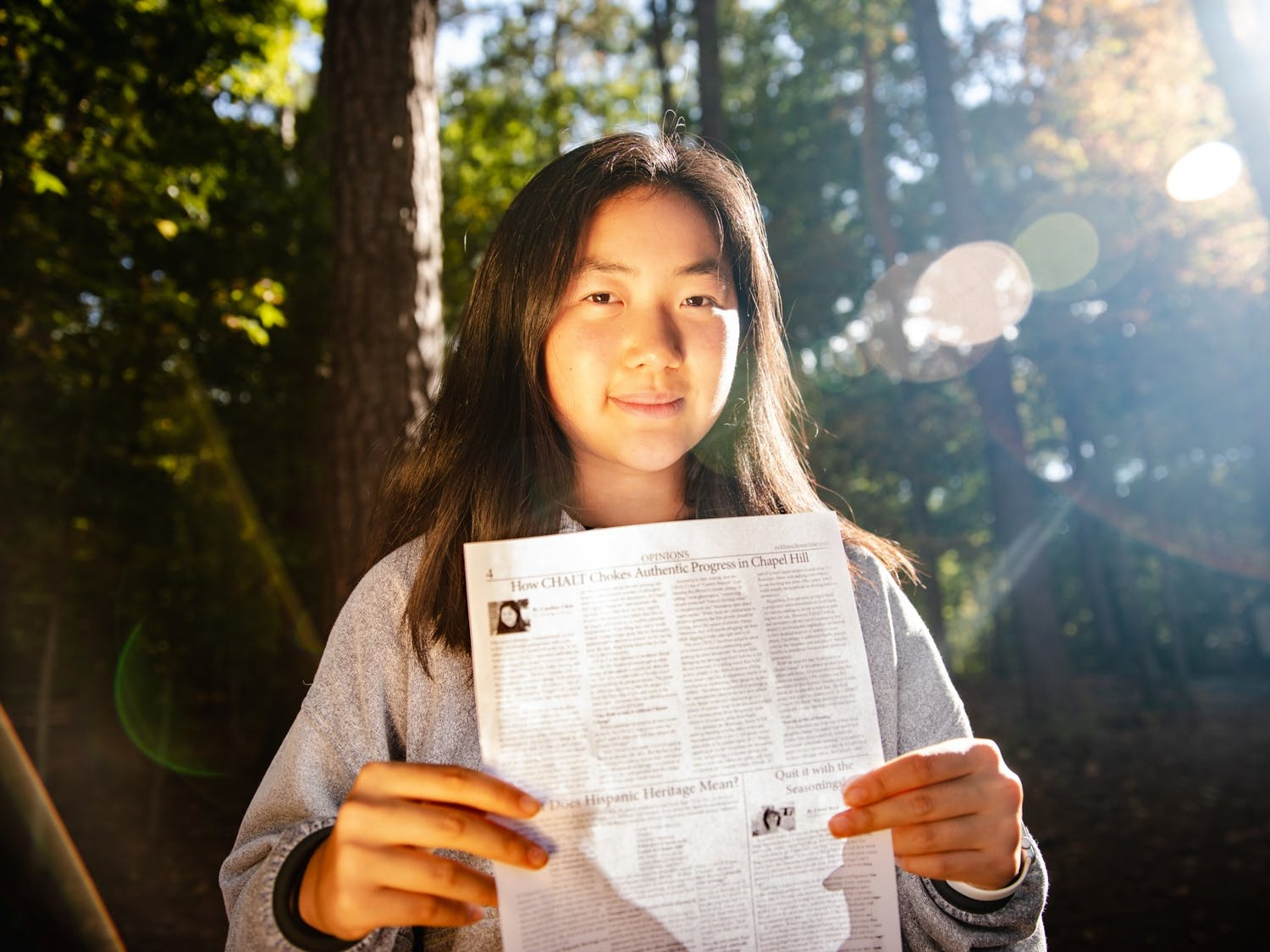"""Caroline Chen, a senior at East Chapel Hill High School, poses for a portrait with her article """"How CHALT chokes authentic progress in Chapel Hill"""" on Monday, Oct. 25, 2021. Chen's critique of CHALT, a.k.a. the Chapel Hill Alliance for a Livable Town, was originally published in the East Chapel Hill Observer and has since received a direct response from the organization."""