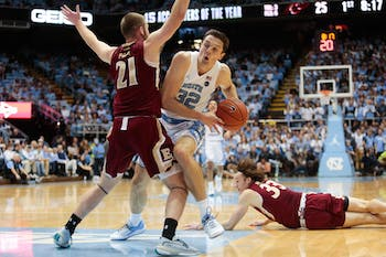 UNC graduate forward Justin Pierce (32) attempts an offensive drive past Elon sophomore guard Andy Pack (21) and junior forward Simon Wright (33) during a game in the Dean Smith Center on Wednesday, Nov. 20, 2019.