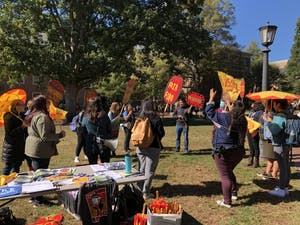 Students practice chants in the quad before the protest Monday.