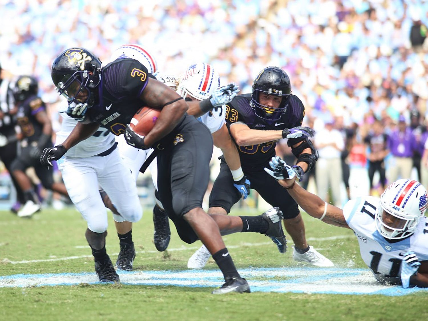 ECU outside receiver Lance Ray (3) breaks the tackle from UNC's defense.