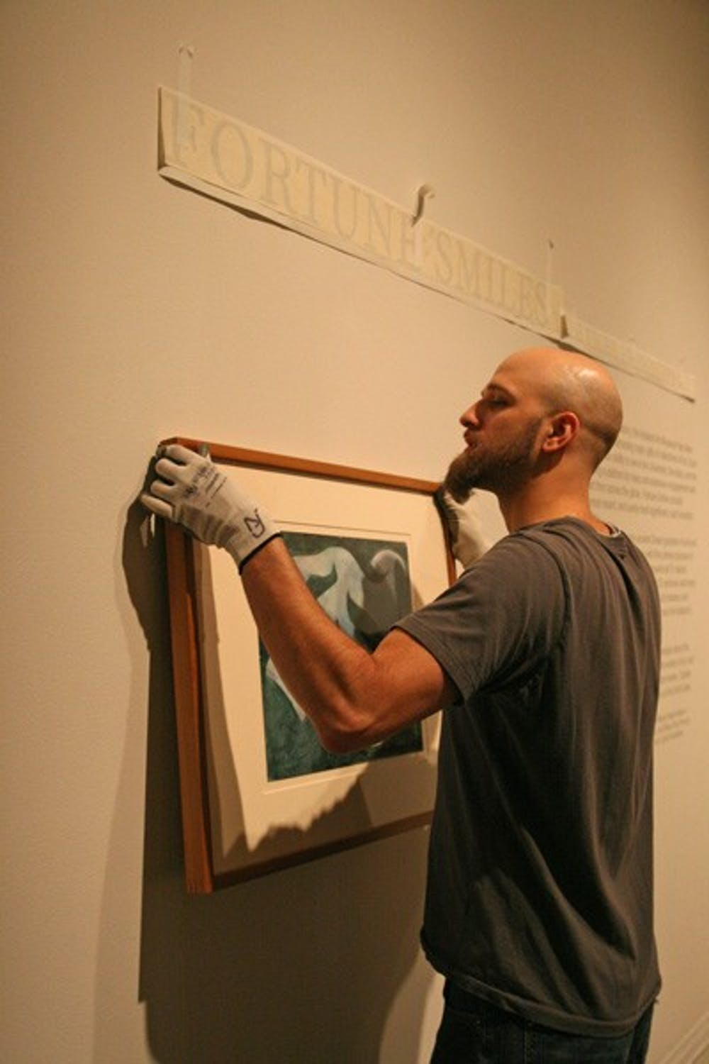 Ackland Art Museum preparator Andrew Nagy hangs a painting for a new exhibit. DTH/Becca Brenner