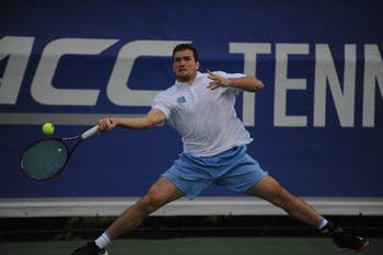 Junior William Blumberg swings at the ball at the ACC tournament semifinals. UNC played against Virginia and lost 3-4. Blumberg won his doubles match with senior Blaine Boyden and lost his singles match.