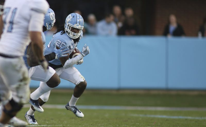 UNC safety Dominquie Green (26) runs back the Tar Heels' first interception of the season for a touchdown.