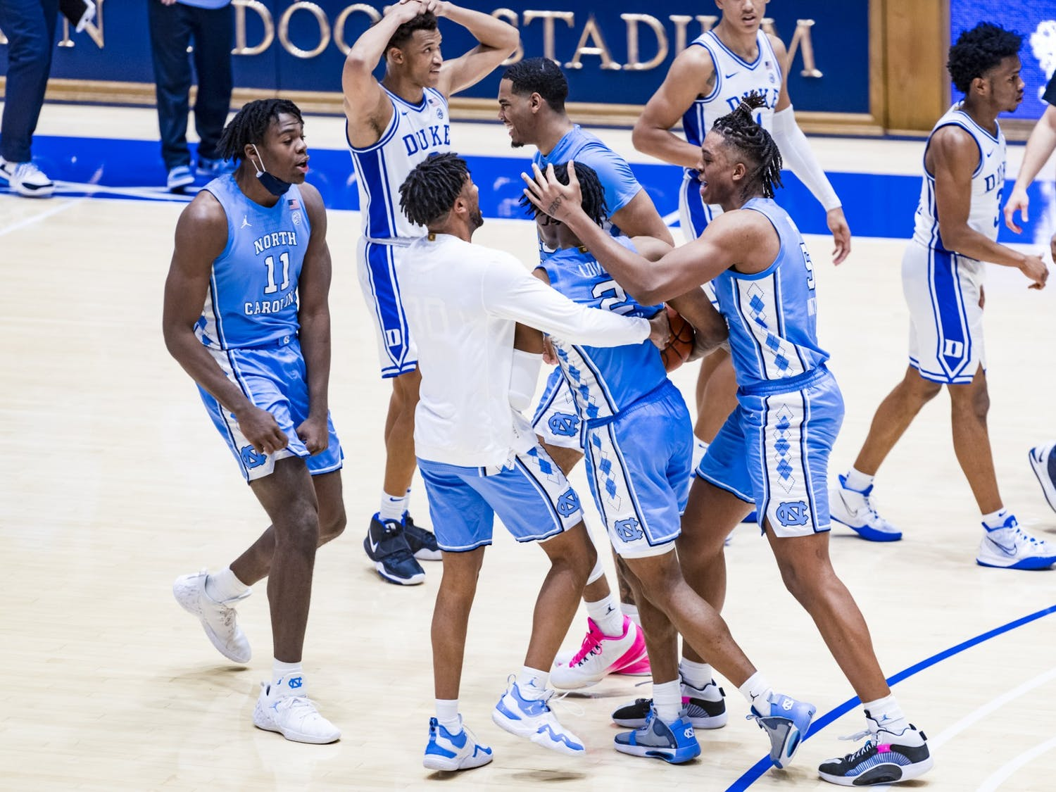 First-year guard Caleb Love (2) is embraced by his teammates following UNC's 91-87 victory over Duke at Cameron Indoor Stadium, Feb 6, 2021. Photo courtesy of Natalie Ledonne.