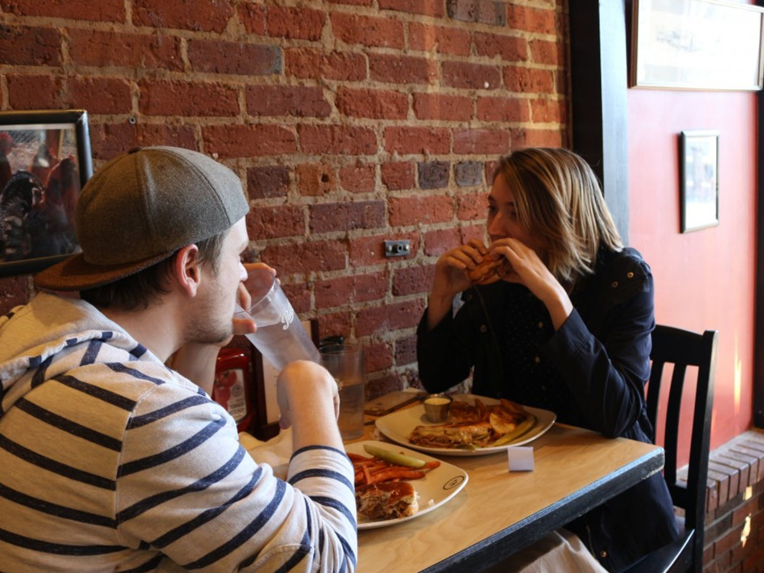 UNC junior Taylor Halterman and Chapel Hill resident Jake Lewis enjoy a meal at Roots, located on Franklin St., on Friday, Jan. 25, 2019. The restaurant is closing on Feb. 17, 2019 and plans to reopen in Durham. One of the owners, Gabriel Ordonez, wants to promote the new location by giving coupons to customers that visit the Franklin location before it closes.