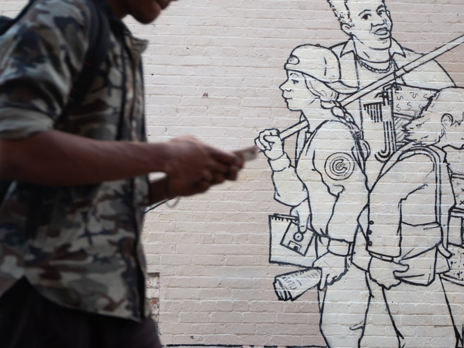 """A student passes by a mural outside of Carolina Coffee Shop on Tuesday, Feb. 5, 2019. The mural, titled """"Parade of Humanity"""" and created by Michael Brown, was restored in 2008 and stands as one of several pieces of public art in Chapel Hill."""