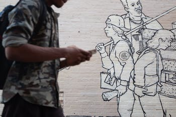 "A student passes by a mural outside of Carolina Coffee Shop on Tuesday, Feb. 5, 2019. The mural, titled ""Parade of Humanity"" and created by Michael Brown, was restored in 2008 and stands as one of several pieces of public art in Chapel Hill."