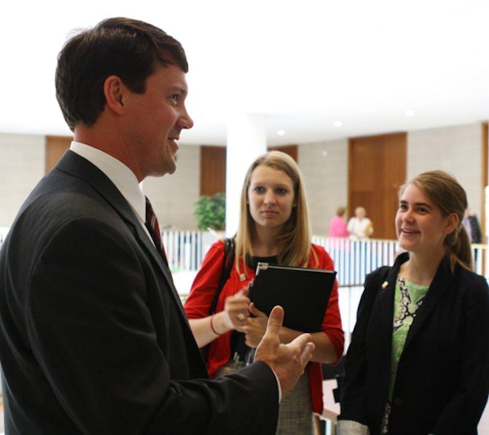 <p>Sen. Dan Soucek, R-Alexander, speaks with Chandler Thompson, N.C. State University's student body president, and Mary Cooper.</p>