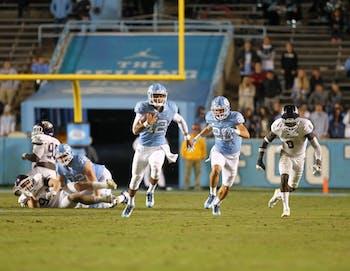 Quarterback Chazz Surratt (12) scrambles against Western Carolina on Saturday in Kenan Stadium.