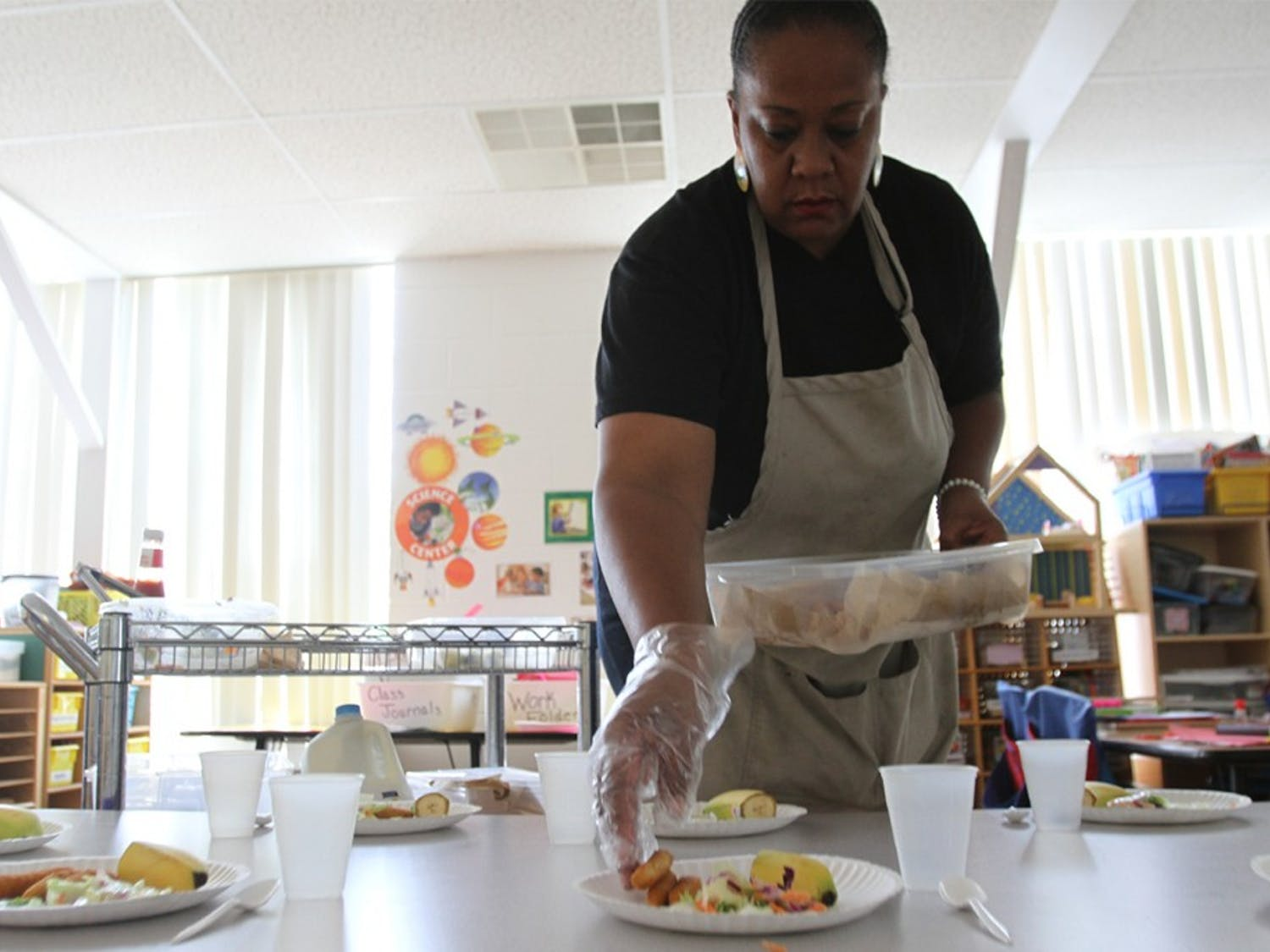 Sonya Dixon, known as Ms. Cookie, cooks and serves lunch at Learning Expressions Childcare Center on Thursday.