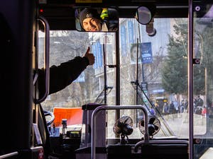 Chapel Hill Transit U bus driver gives thumbs up signal as he approaches the bus stop outside of the UNC Student Stores