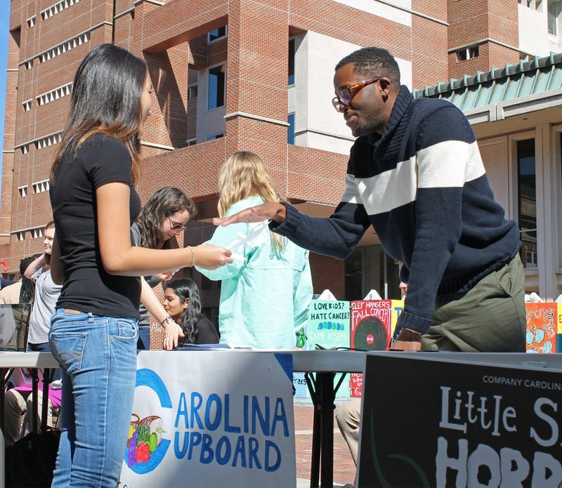 Roderick Gladney, founder of Carolina Cupboard, an organization that provides free food to the UNC campus community, helps recruit new members in the Pit.