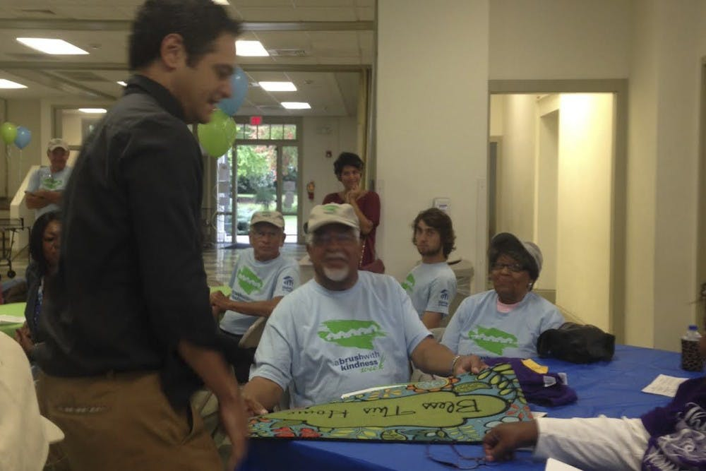 <p>Mayor Mark Kleinschmidt (left) presents Prince (center) and Jean Taylor with a doormat and T-shirts.</p>