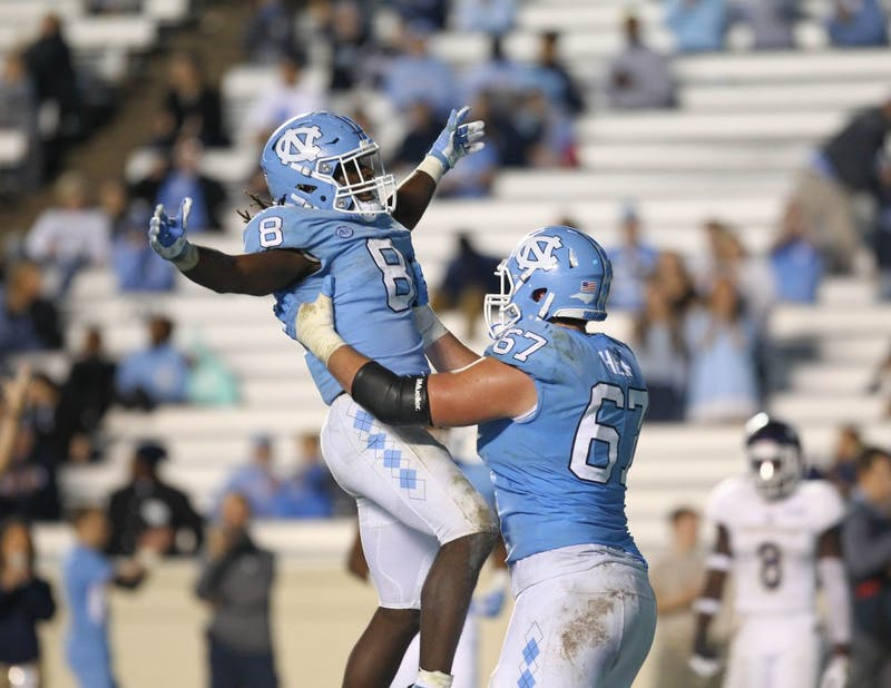 Running back Michael Carter (8) celebrates with offensive lineman Charlie Heck (67) after scoring a touchdown against Western Carolina on Saturday in Kenan Stadium.