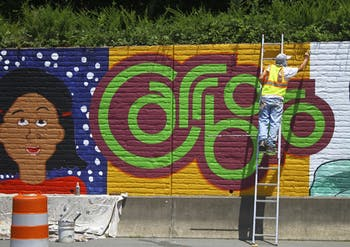 UNC graduate Michael Brown paints a mural for the City of Carrboro off of Jones Ferry Road on Tuesday afternoon.