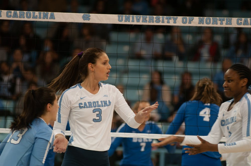 <p>Aristea Tontai (3) reacts to a score with teammates Mia Fradenburg (13) and Destiny Cox (1) during UNC Volleyball's 3-0 win over Duke on Thursday, Nov 21, 2020 in Carmichael Arena.&nbsp;</p>