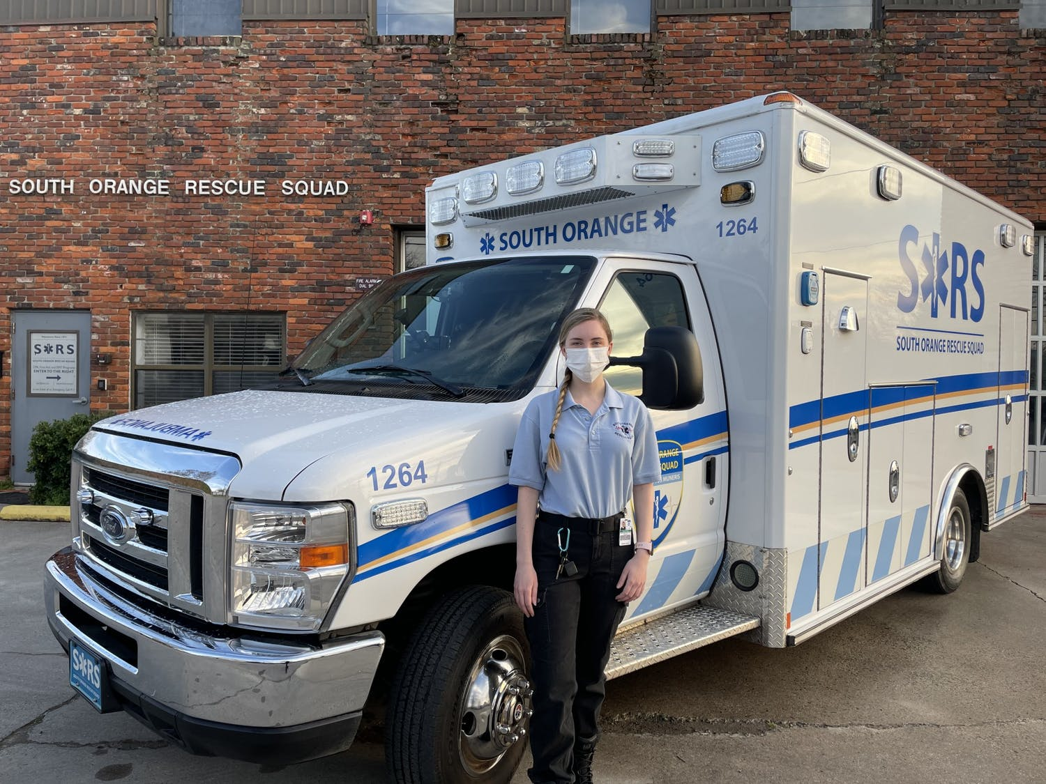 """Senior biology major and SORS volunteer Olivia Nichols poses in front of the South Orange Rescue Squad ambulance. Nichols said of SORS, """"I just feel a community with them. They're very supportive."""" Photo courtesy of Spencer Lindgren/South Orange Rescue Squad"""