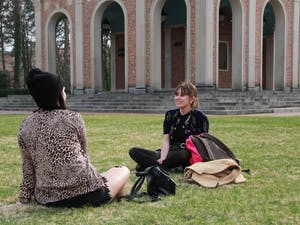 Two students sit and talk on the lawn in front of the bell tower on March 9, 2021.