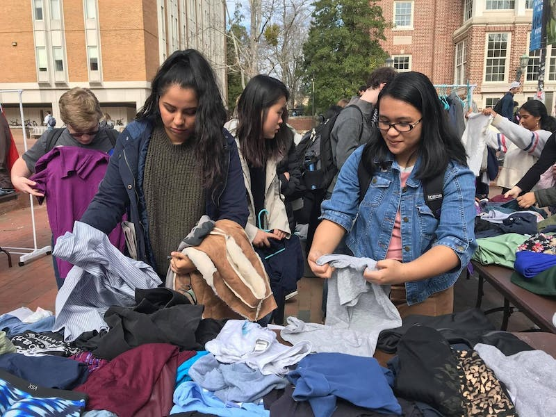 Students picking out clothing at last year's Feminist Clothing Swap, hosted by Carolina Advocates for Gender Equity (CAGE). This year, the 3rd annual Feminist Clothing Swap will be held on Feb. 17 in the Pit. Photo courtesy of Bailey Fattorusso.