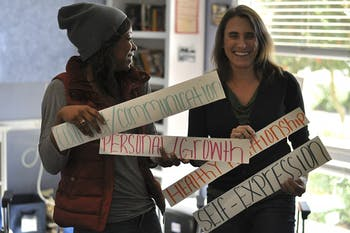 """The YMCA Boomerang Program provides a place for suspended students to receive mentoring and complete school work. Program Manager Shayne Moore (left) and Program Director Tami Pfeifer hold cards with words used as """"themes of the day."""""""