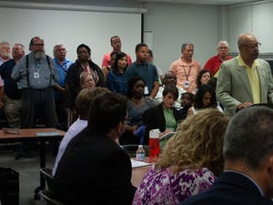 Chapel Hill-Carrboro City Schools bus drivers and monitors rise during a public comments session at the Board of Education work session on Thursday, Oct. 3, 2019 in Chapel Hill, N.C.