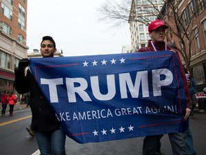 Two Trump supporters carry a banner embroidered with his name through the streets of Washinton on Inauguration Day.