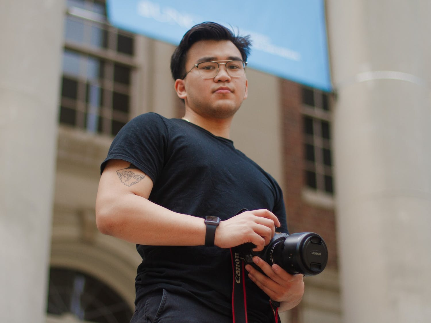 """Nash Consing, a senior studying visual journalism and communications, poses for a portrait in front of Carroll Hall on Sunday, Apr. 11, 2021. """"We experience the trauma [of being Asian-American] every day, """" says Consing. """"So why not capitalize on the joy too?"""""""