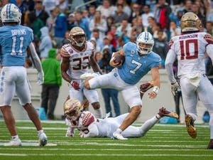 UNC junior quarterback Sam Howell (7) evades a tackle attempt during the second quarter of the Tar Heels' home football matchup in Kenan Stadium on Oct. 9 against the Florida State Seminoles. FSU won 35-25.