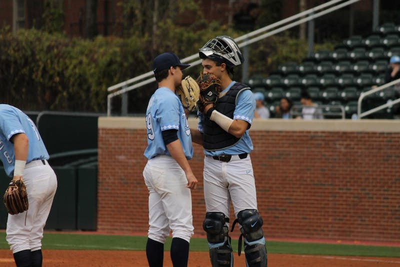 Sophomore Brandon Martorano (4) talks to senior Brett Daniels (19) as Daniels prepares to pitch against East Carolina on Feb. 25 at Boshamer Stadium.
