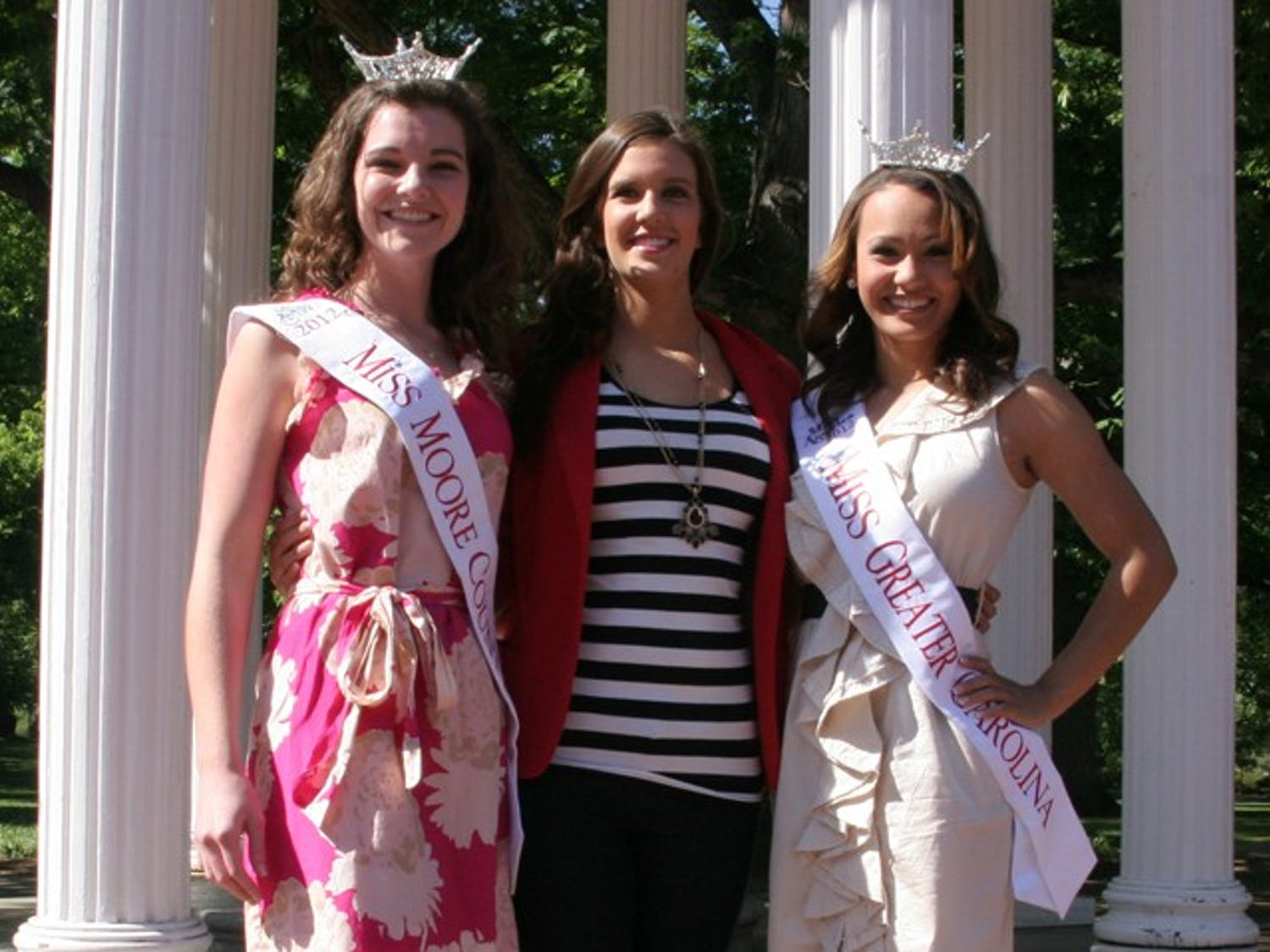 Miss NC Pageant contestants in front of the Old Well. Summer Hennings (pink dress), Dominque Alston (beige dress), Maddisson Sheppard (no crown or sash)