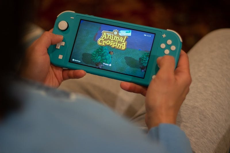 DTH Photo Illustration. A woman plays Animal Crossing: New Horizons on a Nintendo Switch Lite. Animal Crossing: New Horizons was released Friday,  March 20, 2020.