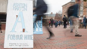 Students walk past campaign signs for student body president candidates Ashton Martin and Jane Tullis in the Pit on Monday, Feb. 11, 2019.