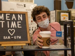 UNC junior environmental studies and business major Maxwell Lewin is a barista and chief sustainability officer at The Meantime Coffee Company, which operates in the lobby of the Campus Y. Lewin delivers a chai latte on Sept. 13.