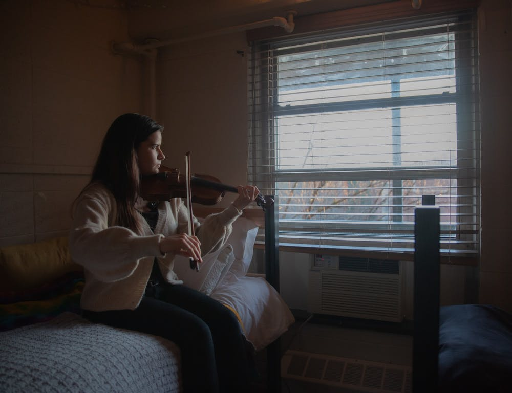<p>DTH Photo Illustration. A student plays the violin in her room at on Thursday, Jan. 28, 2021. As local musicians are impacted by the pandemic, Tracks Music Library is offering an opportunity for artists to share their work with the community.</p>