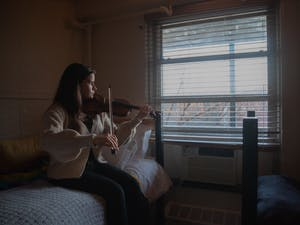 DTH Photo Illustration. A student plays the violin in her room at on Thursday, Jan. 28, 2021. As local musicians are impacted by the pandemic, Tracks Music Library is offering an opportunity for artists to share their work with the community.