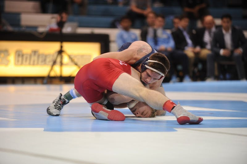 UNC first-year Austin O'Connor gains a takedown against Cornell senior Jonathan Furnas to win the bout through a 23-8 technical fall. No. 9 Cornell defeated UNC 29-5 on Saturday, Feb. 17, 2019 in Carmichael Arena.   (On Saturday, February 17 2019, UNC Wrestling was defeated by Cornell with a score of 29-5. Cornell's head coach, Rob Koll is a '88 former Tar Heel wrestler. He was recognized at the match and gifted a framed Carolina singlet. His success at Carolina accredited Koll as a four-time All American, three-time ACC champion and 1988 NCAA champion at 158 pounds. Koll's collegiate-level training led him to taking Cornell to six top-five finishes in the NCAA, and defeating his alma mater Saturday night. Tensions were high throughout the night, with yelling and complaints from coaches on both teams directed towards the referees. Redshirt freshman Austin O'Connor was the only victorious Tar Heel, defeating Cornell senior Jonathan Furnas 23-8, with a technical fall in the third period.)