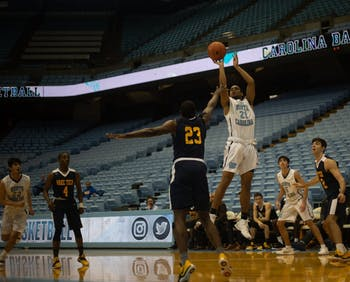 Michael Armstrong (23) attempts to block Nehemiah Stewart (21) from making a basket during a game against Wake Tech on January 15, 2019 at the Dean E. Smith Center. UNC JV won 80-64.