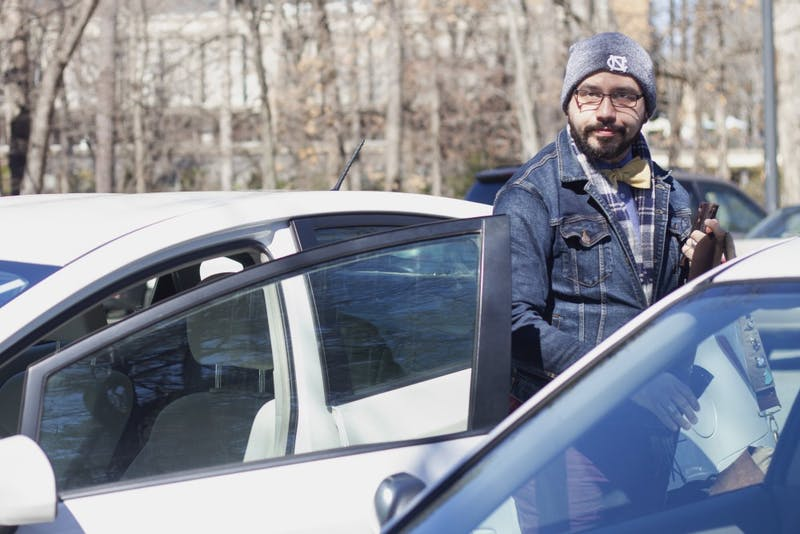 "Logan Brackett, manager for the UNC Department of Romance Studies, exits his car on Stadium Dr. on Wednesday, March 6, 2019. A five-year plan launched by the Department of Transportation and Parking includes provisions for weeknight parking permits, fee increases and new rules to generate revenue. ""It seems like a nickel and dime approach for fees,"" he said. ""Students don't seem like the main beneficiaries here, so it seems odd to charge them."""