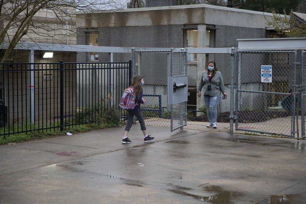 A student of Frank Porter Graham Elementary school walks from carpool toward the school early in the morning on March 26, 2021. CHCCS have recently reopened in-person instruction, although many children are still learning virtually.